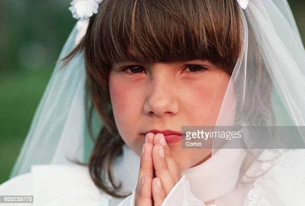 Angela Lowe, wearing her first communion dress, holds up her hands in prayer.