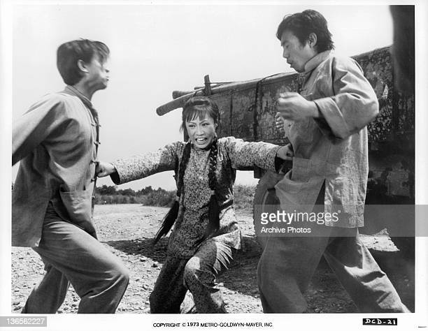 Angela Mao punches the stomachs of two fighting men in a scene from the film 'Deadly China Doll' 1973