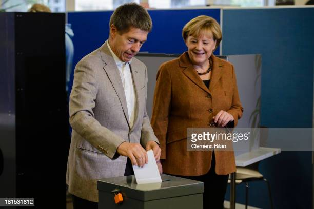 Angela Merkel German Chancellor and Chairwoman of the German Christian Democrats and her husband Joachim Sauer cast their ballot in German federal...