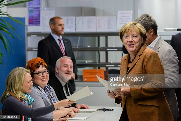 Angela Merkel German Chancellor and Chairwoman of the German Christian Democrats and her husband Joachim Sauer arrive before casting their ballots in...