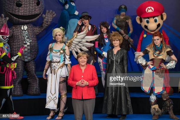 Angela Merkel Germany's chancellor and Christian Democratic Union leader poses for a photograph with a group of cosplayers at Gamescom video games...