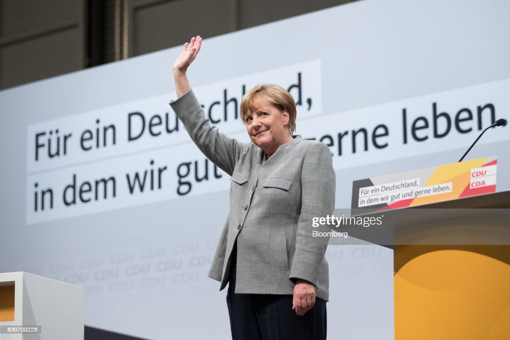 Angela Merkel, Germany's chancellor and Christian Democratic Union (CDU) leader, center, waves to the crowd after speaking during a campaign event in Dortmund, Germany, on Saturday, Aug. 12, 2017. Merkelopened her re-election campaign with criticism of the nations auto executives, saying they need to embrace new technology more quickly to protect jobs and repair damage done by adiesel cheating scandal. Photographer: Jasper Juinen/Bloomberg via Getty Images