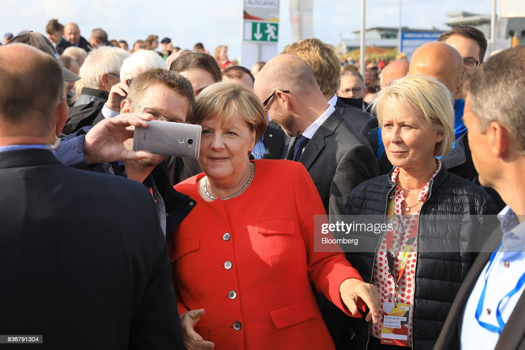 Angela Merkel, Germany's chancellor and Christian Democratic Union (CDU) leader, center, poses for a 'selfie' photo with supporters during an election campaign stop in Saint Peter-Ording, Germany, on Monday, Aug. 21, 2017. Merkel headed out on the campaign trail last week and quickly faced disruption by anti-immigration demonstrators, a reminder that the refugee crisis that sent her popularity plunging in 2016 remains a residual risk. Photographer: Krisztian Bocsi/Bloomberg via Getty Images