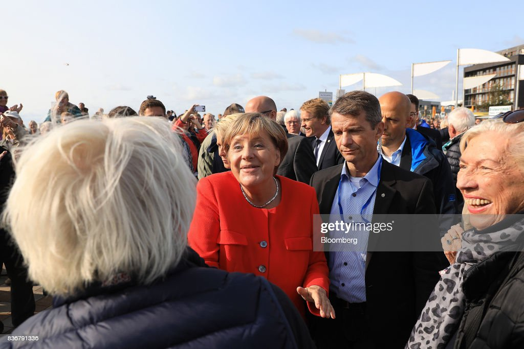 Angela Merkel, Germany's chancellor and Christian Democratic Union (CDU) leader, center, greets supporters as she arrives for an election campaign stop in Saint Peter-Ording, Germany, on Monday, Aug. 21, 2017. Merkel headed out on the campaign trail last week and quickly faced disruption by anti-immigration demonstrators, a reminder that the refugee crisis that sent her popularity plunging in 2016 remains a residual risk. Photographer: Krisztian Bocsi/Bloomberg via Getty Images