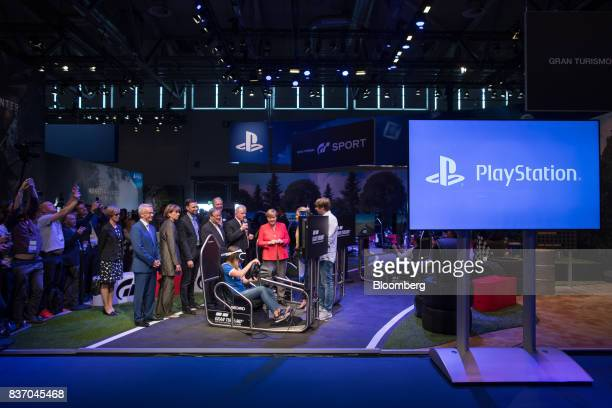 Angela Merkel Germany's chancellor and Christian Democratic Union leader center visits the Sony Corp PlayStation exhibition stand as an attendee...