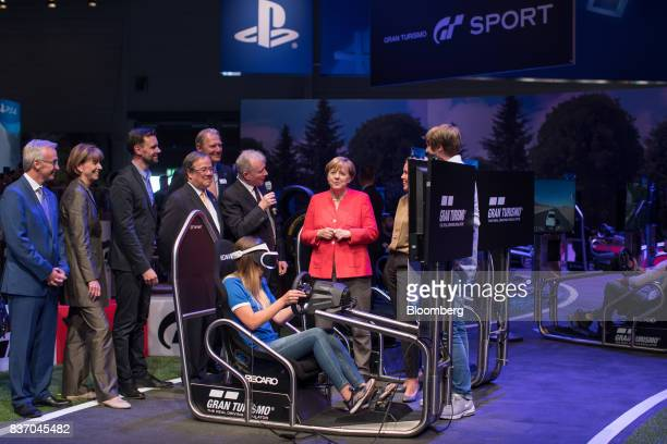 Angela Merkel Germany's chancellor and Christian Democratic Union leader visits the Sony Corp PlayStation exhibition stand as an attendee plays the...
