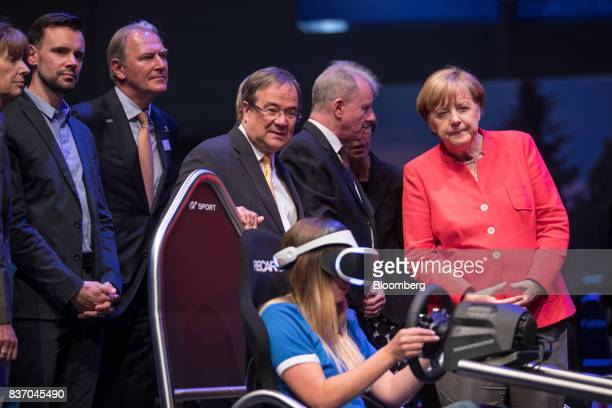 Angela Merkel Germany's chancellor and Christian Democratic Union leader visits the Sony Corp PlayStation exhibition stand and watches as an attendee...