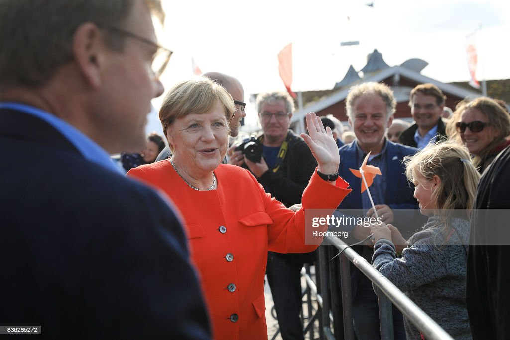 Angela Merkel, Germany's chancellor and Christian Democratic Union (CDU) leader, waves to attendees after speaking during an election campaign stop in Saint Peter-Ording, Germany, on Monday, Aug. 21, 2017. Merkel headed out on the campaign trail last week and quickly faced disruption by anti-immigration demonstrators, a reminder that the refugee crisis that sent her popularity plunging in 2016 remains a residual risk. Photographer: Krisztian Bocsi/Bloomberg via Getty Images