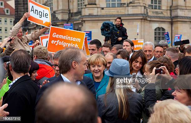Angela Merkel Germany's chancellor and party leader of the Christian Democratic Union greets supporters during an election rally in Dresden Germany...