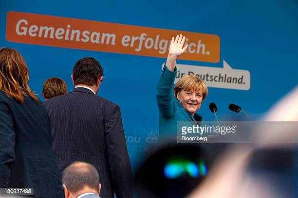 Angela Merkel Germany's chancellor and party leader of the Christian Democratic Union waves to the crowd during an election rally in Dresden Germany...