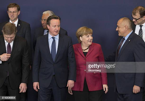 Angela Merkel Germany's chancellor center right stands beside David Cameron UK prime minister center left ahead of a family photograph during a...