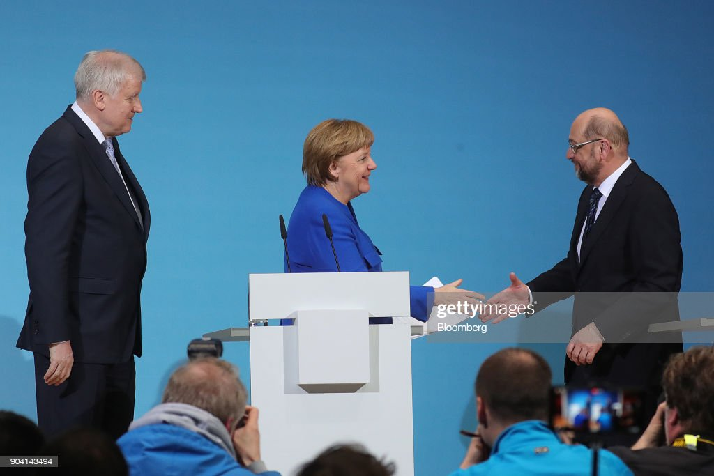 Angela Merkel, Germany's chancellor, center, shakes hands with Martin Schulz, leader of the Social Democrat Party (SPD), right, as Horst Seehofer, leader of the Christian Social Union (CSU) party, looks on at the end of a news conference following overnight coalition negotiations, at the SPD headquarters in Berlin, Germany, on Friday, Jan. 12, 2018. After a marathon of more than 24 hours of talks to end Germanys political gridlock, leaders of Merkels Christian Democratic Union, her Bavarian sister party and the Social Democrats hammered out a 28-page agreement. Photographer: Krisztian Bocsi/Bloomberg via Getty Images