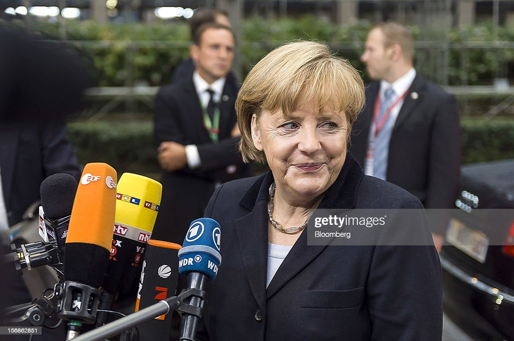 Angela Merkel, Germany's chancellor, center, speaks to the media as she arrives for the European Union (EU) leaders summit at the European Council headquarters in Brussels, Belgium, on Friday, Nov. 23, 2012. European Union leaders deadlocked over the bloc's next seven-year budget, adding to the quarrels between rich and poor countries that have stymied the response to the euro debt crisis. Photographer: Jock Fistick/Bloomberg via Getty Images