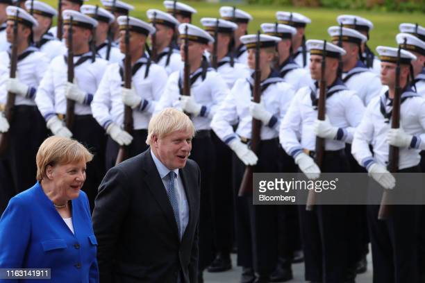 Angela Merkel Germany's chancellor left and Boris Johnson UK prime minister review an honor guard at the Chancellery in Berlin Germany on Wednesday...