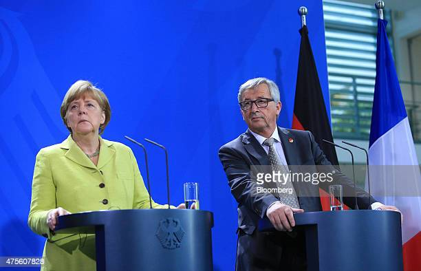 Angela Merkel Germany's chancellor left and JeanClaude Juncker European commission president pause during a news conference in Berlin Germany on...