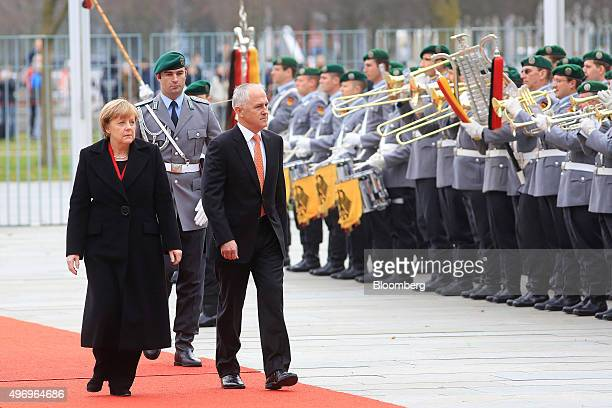 Angela Merkel Germany's chancellor left and Malcolm Turnbull Australia's prime minister review an honour guard during a welcoming ceremony prior to a...