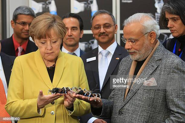 Angela Merkel Germany's chancellor left and Narendra Modi India's prime minister hold robotic ants manufactured by Festo KG as they visit the...