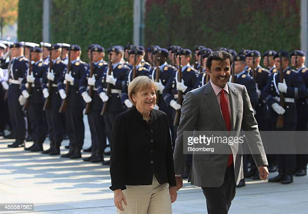 Angela Merkel Germany's chancellor left and Sheikh Tamim bin Hamad Al Thani the Emir of Qatar review an honour guard ahead of a news conference at...
