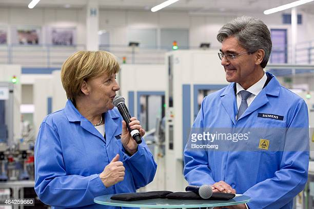 Angela Merkel Germany's chancellor left speaks into a microphone as she stands with Joe Kaeser chief executive officer of Siemens AG on the automated...