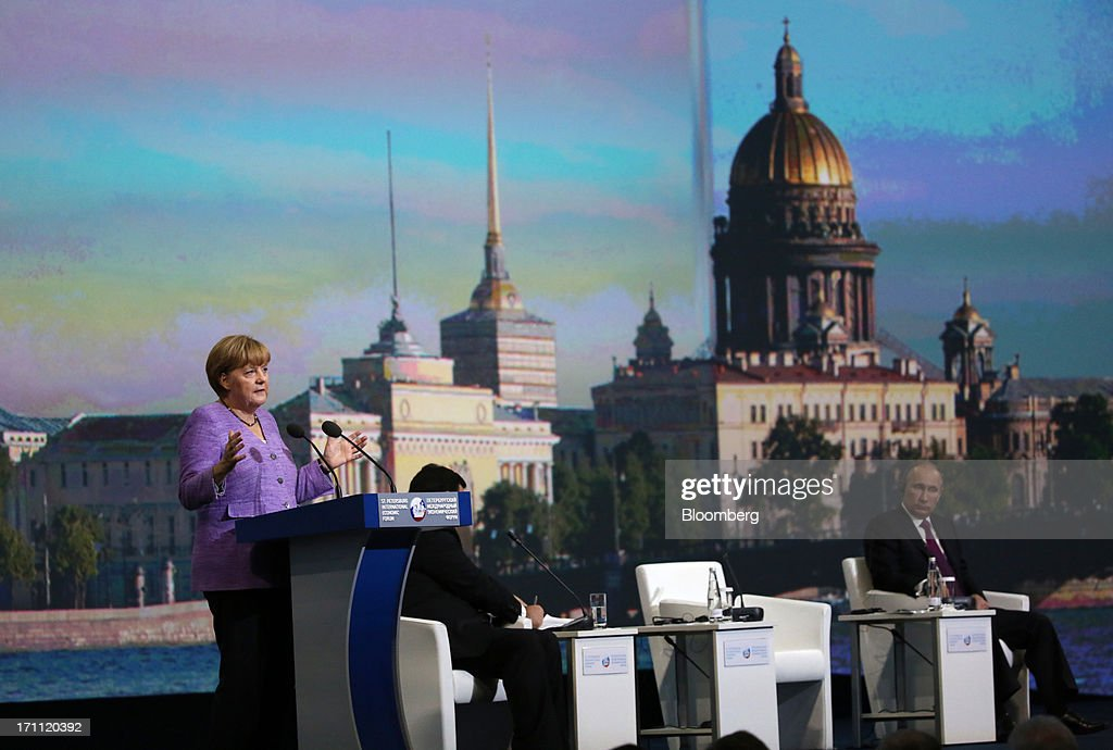 Angela Merkel, Germany's chancellor, left, speaks while Vladimir Putin, Russia's president, right, listens on day two of the St. Petersburg International Economic Forum 2013 (SPIEF) in St. Petersburg, Russia, on Friday, June 21, 2013. Putin is battling investor skepticism to woo foreign executives descending on his hometown today as Russia's economy faces a risk of recession and a crackdown on critics scares off intellectuals. Photographer: Andrey Rudakov/Bloomberg via Getty Images
