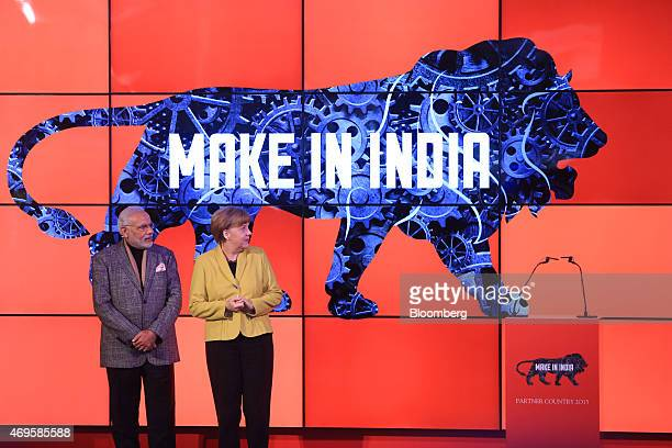 Angela Merkel Germany's chancellor right and Narendra Modi India's prime minister stand on stage as a 'Make In India' logo is displayed at the...