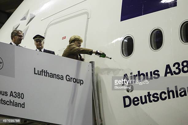Angela Merkel Germany's chancellor right pours champagne onto the fuselage of an Airbus A380 aircraft as Carsten Spohr chief executive officer of...