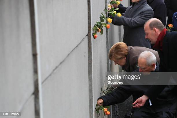 Angela Merkel, Germany's chancellor, third from front, and Wolfgang Schaeuble, president of the German Bundestag, second from front, place roses into...