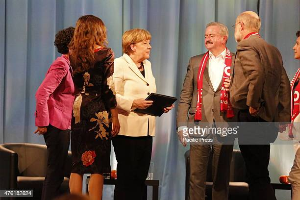 Angela Merkel talks with the panel members after the discussion has ended The German Chancellor Angela Merkel took part in a panel discussion about...
