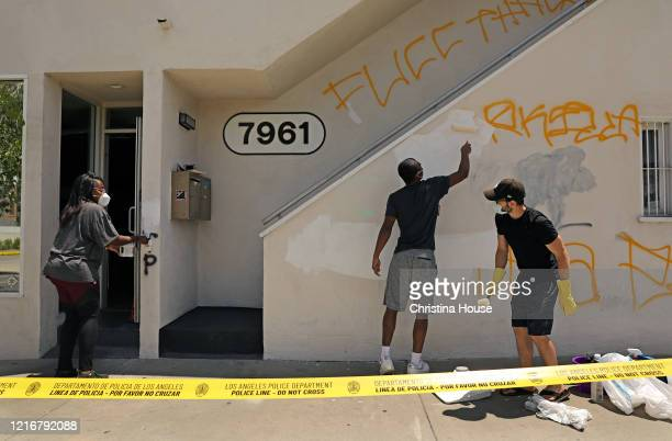 Angela Proctor left with her son Nikolas Steed center get a helping hand from neighbor Chris Hendrickson right while covering up graffiti on the...