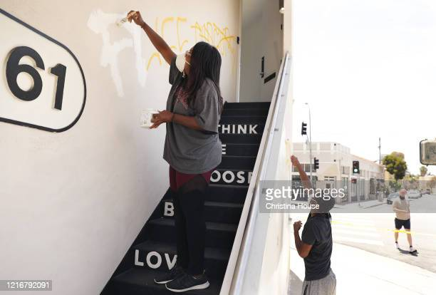 Angela Proctor left with her son Nikolas Steed right cover up graffiti on the building that houses Wayfarer a social impact production company that...