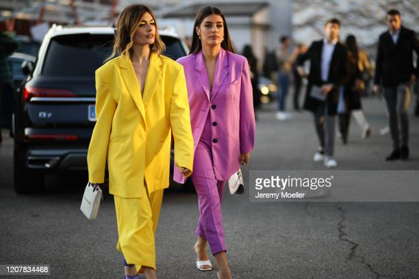 Angela Rozas Saiz wearing a yellow suit and Aida Domenech wearing a purple suit are seen during Milan Fashion Week Fall/Winter 2020-2021 on February...