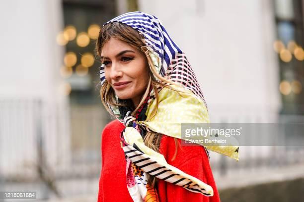 Angela Rozas Saiz wears a Bimba Y Lola scarf over the head, a red wool pullover, outside Leonard Paris, during Paris Fashion Week - Womenswear...