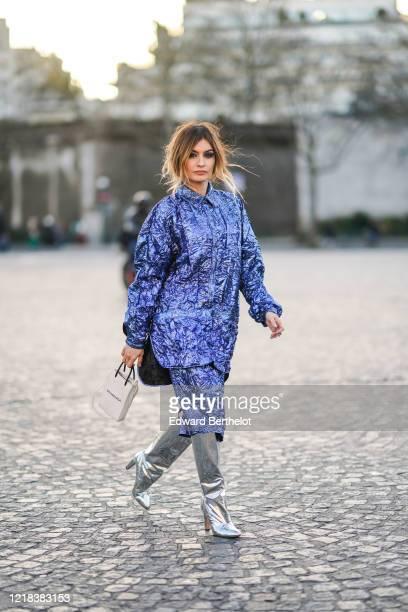 Angela Rozas Saiz wears a blue shiny dress a Balenciaga white bag silver shiny pointy high boots outside Rochas during Paris Fashion Week Womenswear...