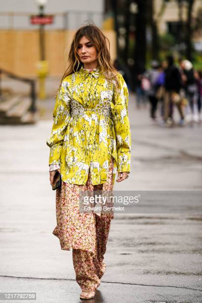 Angela Rozas Saiz wears a yellow dress with printed elephants, pink and red floral print flowing pants, outside Ann Demeulemeester, during Paris...