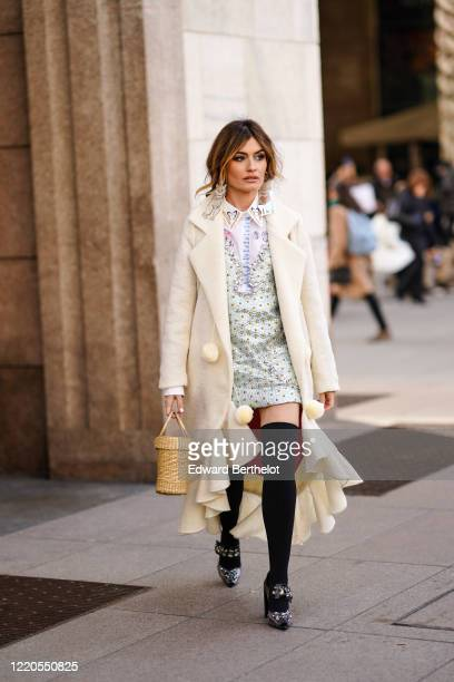 Angela Rozas Saiz wears catshaped earrings a white ruffled long coat with fluffy pompoms a pale green lustrous silky dress over a white shirt with...