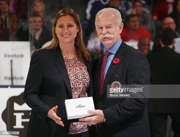 Angela Ruggeiero receives her Hockey Hall of Fame blazer from the Chairman of the Hockey Hall of Fame Lanny McDonald prior to the Legends Classic...