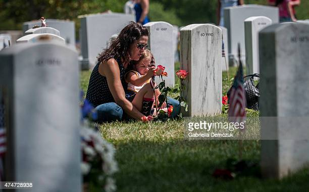 Angela Spraul and her daughter Ava sit at the grave of her husband John Spraul US Navy who died Feb 28 at Section 60 on Memorial Day at Arlington...