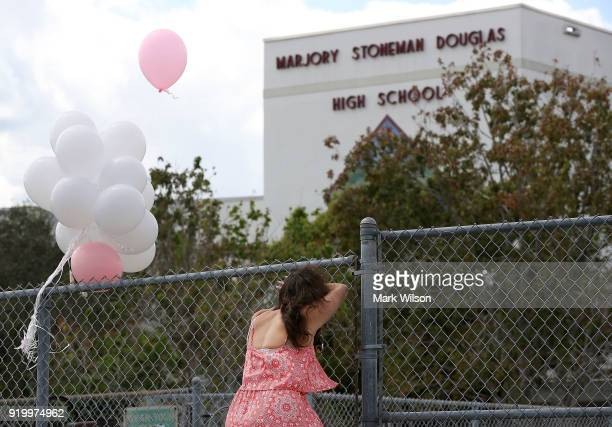 Angela Tanner rests against the fence that surrounds the Marjory Stoneman Douglas High School on February 18 2018 in Parkland Florida Police have...