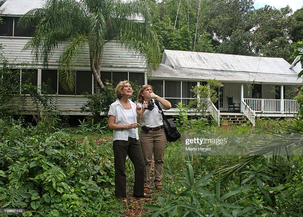 Angela Withers, president of the Henry Nehrling Society, left, and Theresa Schretzmann-Myers, past president, in the garden behind the Nehrling house.
