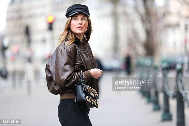 Angelica Ardasheva fashion blogger from Angy's Tea Room is wearing a black beret hat a brown leather aviator jacket with fur and a patched logo on...