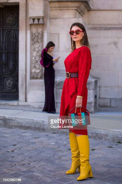 Angelica Ardasheva wearing a red midi dress Red Valentino yellow boots and striped colorful bag is seen after the Paco Rabanne show on September 27...