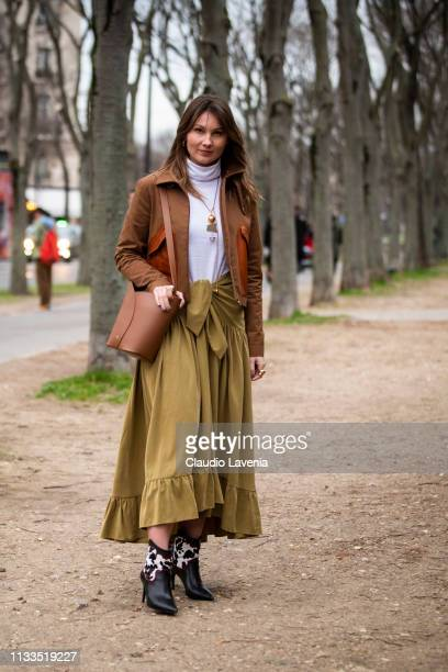 Angelica Ardasheva wearing a white turtleneck top green skirt black boots brown jacket and brown bag is seen outside Valentino on Day 7 Paris Fashion...