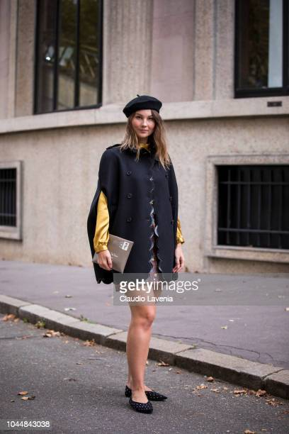 Angelica Ardasheva wearing a yellow top checked mini skirt black cape black beret beige clutch and black shoes is seen after the Miu Miu show on...