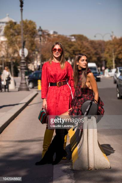 Angelica Ardasheva wearing red midi dress and Red Valentino yellow boots and Sara Rossetto wearing checked mini dress with over the knees black boots...
