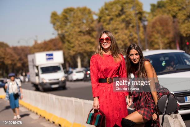 Angelica Ardasheva wearing red midi dress and Sara Rossetto wearing checked mini dress and black bag are seen after the Paco Rabanne show on...