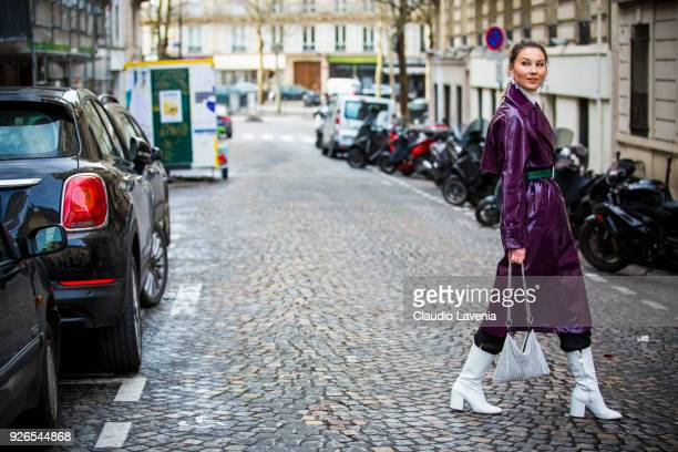 Angelica Ardasheva wearing violet laminated trench green belt and white heels boots is seen in the streets of Paris after the Nina Ricci show during...
