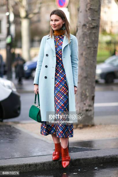 Angelica Ardasheva wears a blue coat a multicolor dress a green bag and red shoes outside the Mashama show during Paris Fashion Week Womenswear...