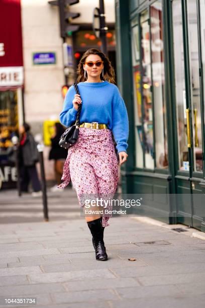Angelica Ardasheva wears a blue wool pullover a golden belt a pink floral print skirt outside Valentin Yudashkin during Paris Fashion Week Womenswear...