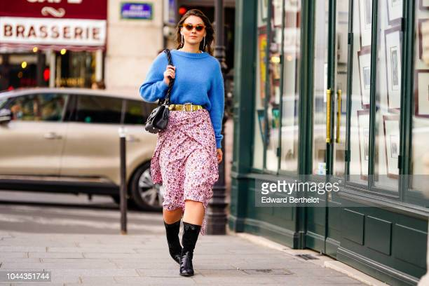 Angelica Ardasheva wears a blue wool pullover a golden belt a pink floral print skirt outside Valentin Yudashkin during Paris Fashion Week Womenswear...