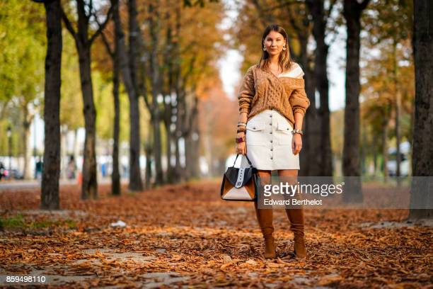 Angelica Ardasheva wears a camel Vneck pullover a white skirt camel boots and a black and camel bag outside the Rochas show during Paris Fashion Week...